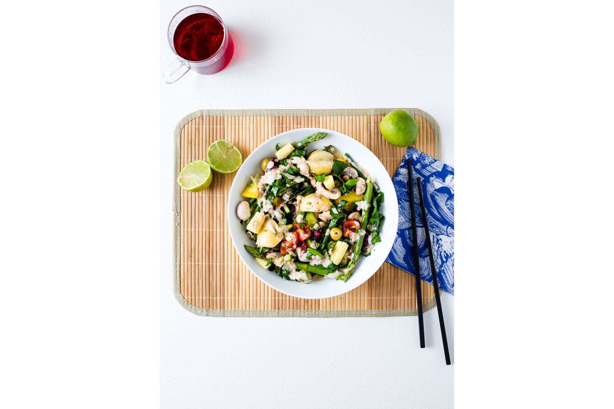 A bowl of warm Asian inspired salad with a glass of hibiscus tea www.realfamilyjourney.com