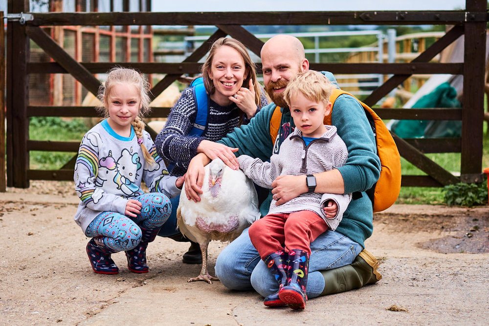 A family petting a rescued turkey at a sanctuary