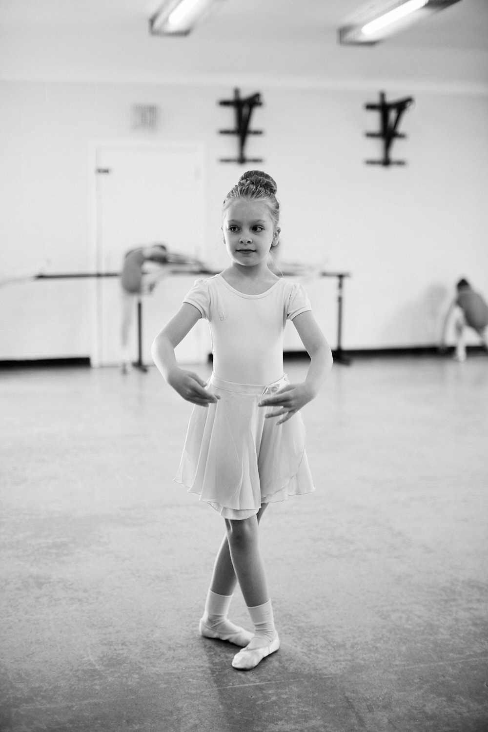 A young ballet dancer posing for the photo in black and white