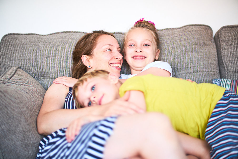 Young children having a cuddle with their mum on the sofa