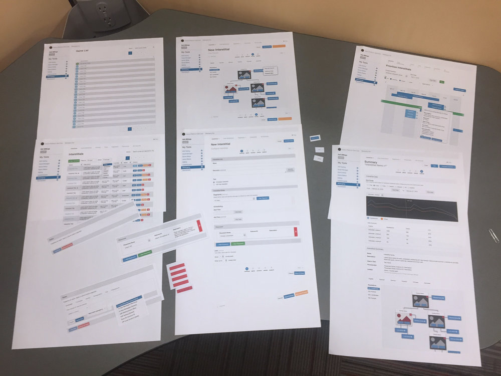 The original paper prototypes splayed out on a table. You can see some of the bits used to alter the page content depending on the form's state.
