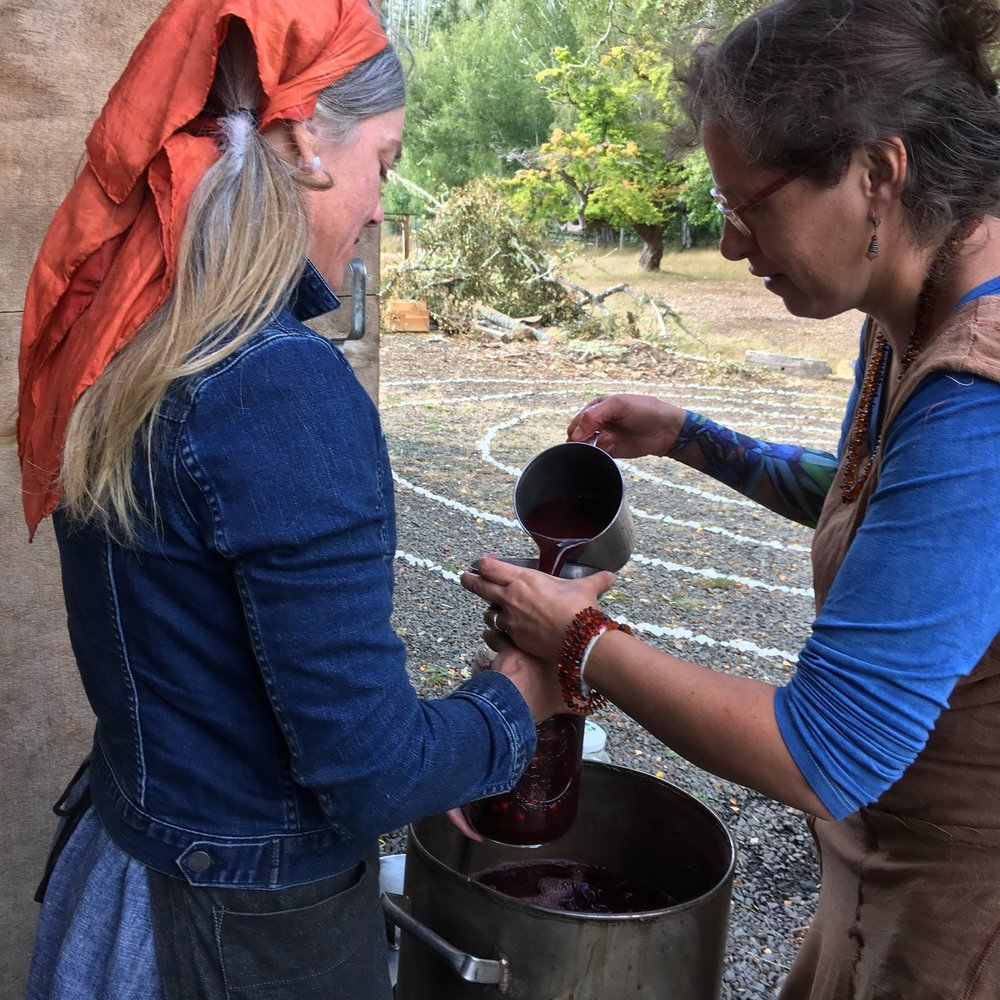 Filling a cauldron containing cloth with Queen Madder Dye Bath