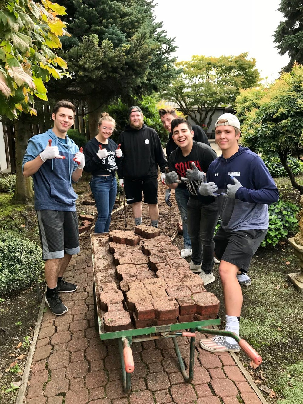 September - PUYALLUP FOURSQUARE MINISTRY INSTITUTEAn incredibly fun and enthusiastic group of college students from the Puyallup Foursquare Ministry Institute brought their muscles to Step By Step and checked off an impressive To-Do list, in less than 2 hours!They tackled the first demolition project of our remodel (pulling up patio pavers and stacking them neatly for re-use), set up all the chairs and tables for an event the next day, moved office furniture and greenhouse supplies, and reorganized storage spaces. They also assembled over 1,000 utensil sets for our annual family Christmas event that we will be hosting for our moms and their families in December.We were so blessed by the beautiful hearts of these volunteers, as they smiled and joked together, while working so hard. Thank you for your continued support of Step By Step and the mothers and babies we serve. We hope you will come back again very soon!
