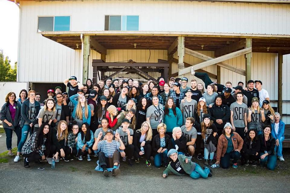 September - Ministry Institute InternsOver 90 students from Puyallup Foursquare Church came out to the farm for a volunteer day. Led by Hannah McGunagle, they worked hard, were incredibly polite, and knocked out jobs that would have taken us weeks to complete! They helped us clear a large weedy area of ground and build stations for our 5K Kids' Obstacle Course, assembled over 1,000 diaper packs for new moms, tied up over 1,200 silverware sets for our upcoming family Christmas dinner and celebration, stuffed 1,000 envelopes for a mailing, helped organize baby clothes and blankets, made Christmas decorations and centerpieces, and muscled around a whole bunch of tables, chairs, and other assorted furniture to make our storage much tidier! We really enjoyed having them and are extremely grateful for all their hard work!