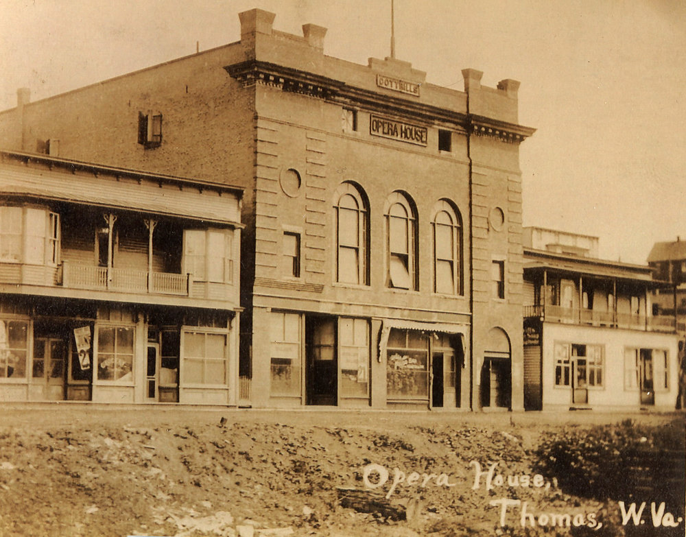 Postcard photograph of Cottrill's Opera House, circa 1909. Note the three arched windows and the circular brick panels.