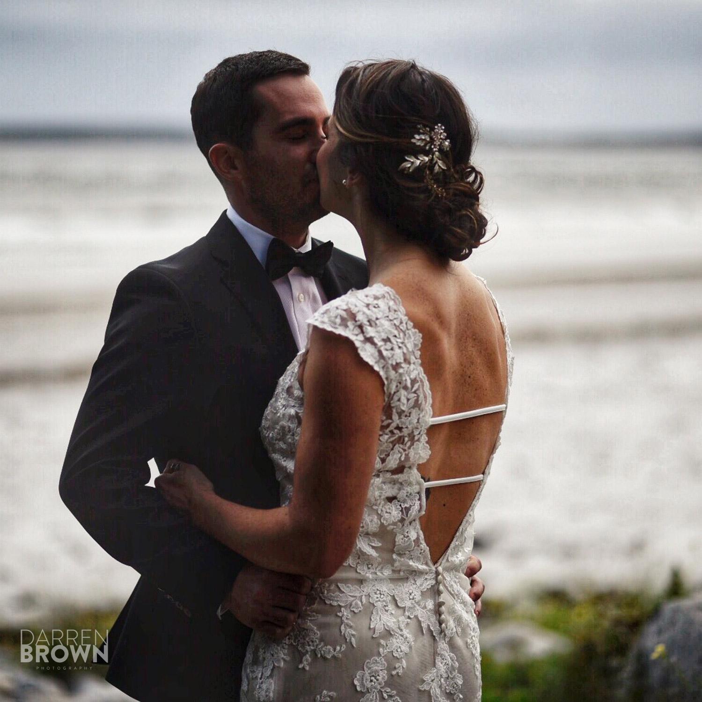 bride and groom kiss by ocean