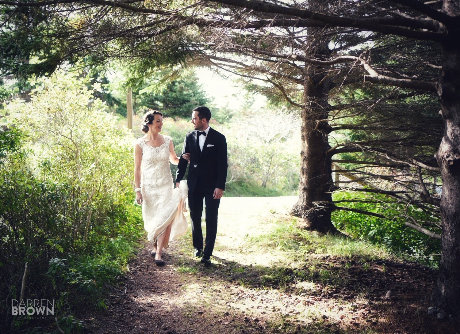 bride and groom walk through woods