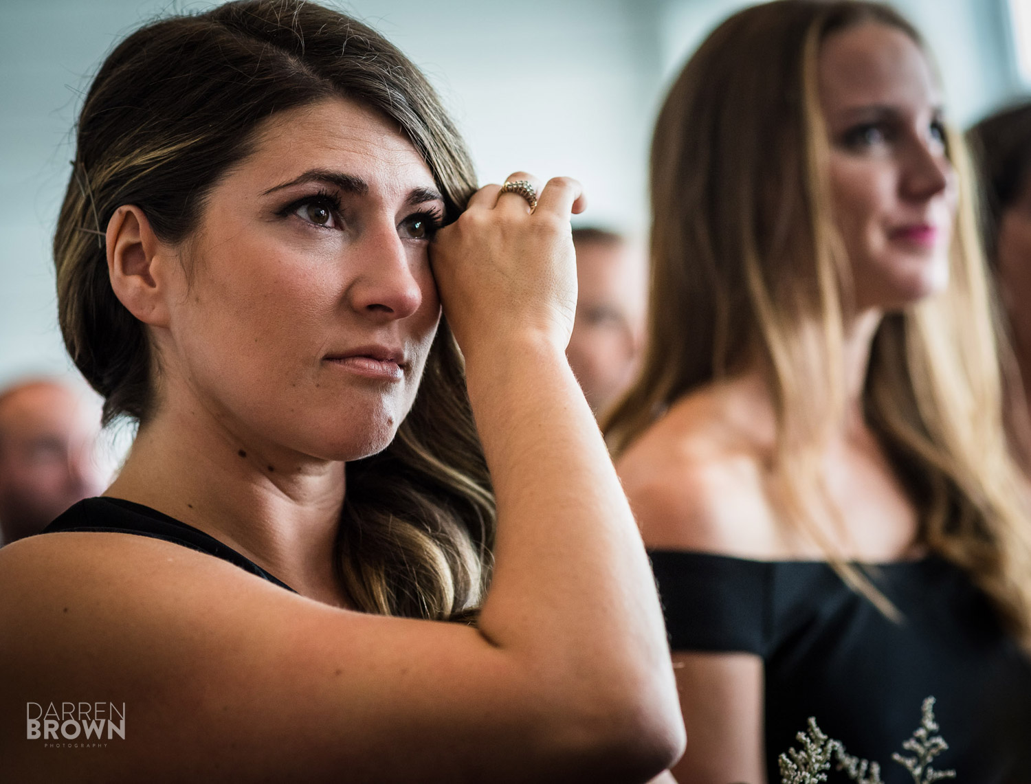 woman wipes tear away during wedding reception