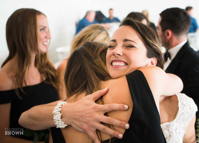 bride hugs bridesmaid after ceremony