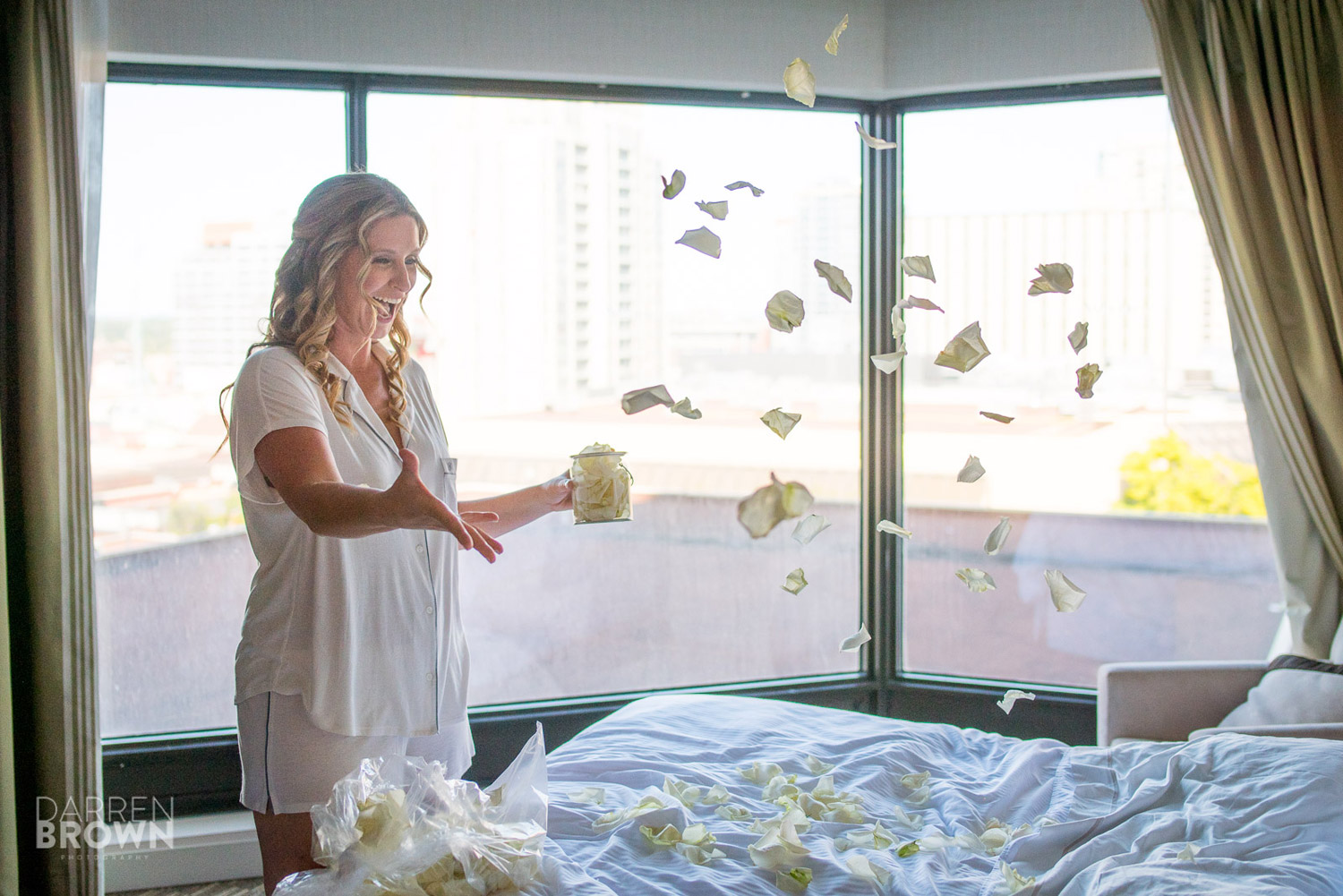 bride throwing flower petals on bed