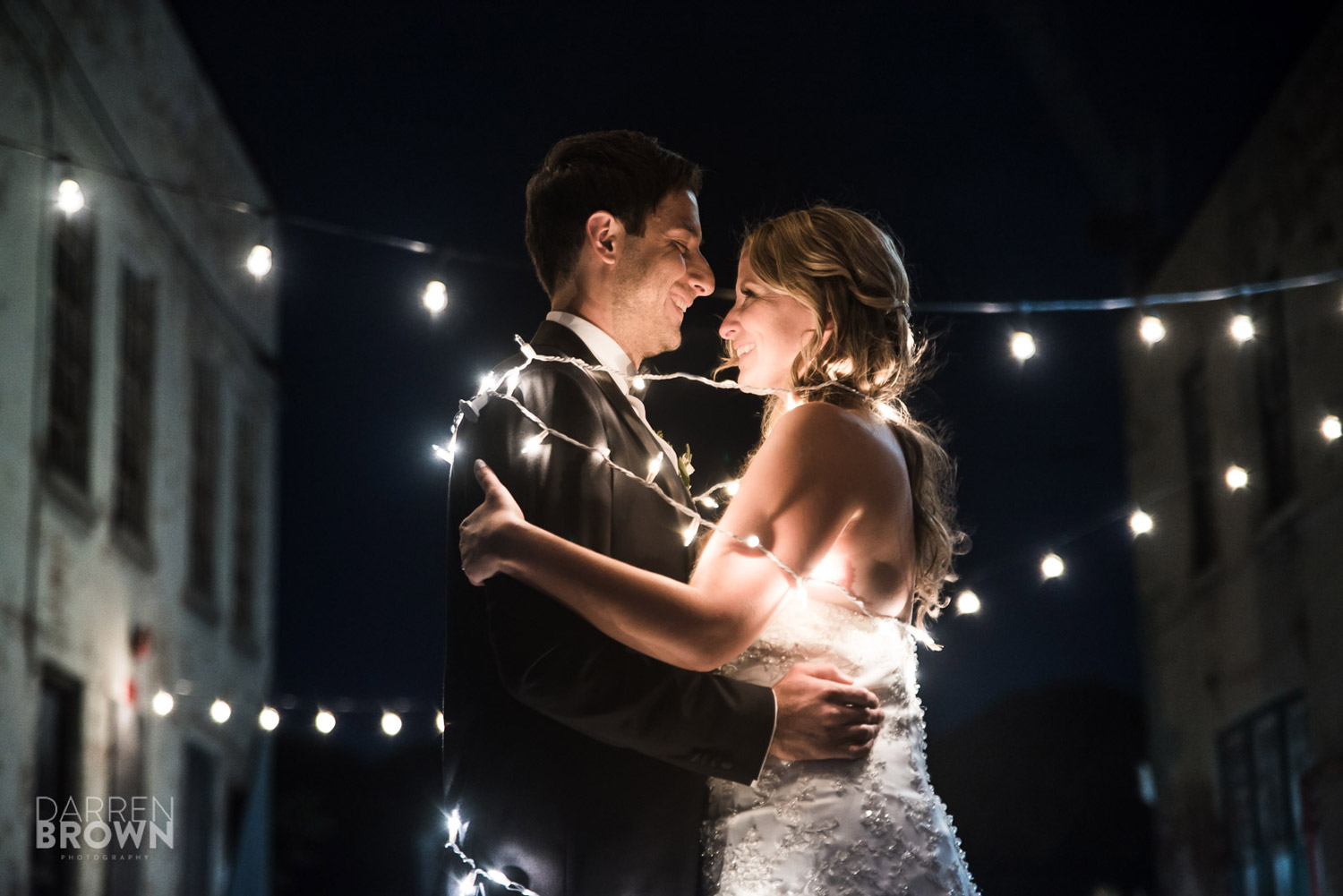 dramatic bride and groom portrait with Christmas lights at Zibi