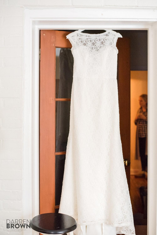 vintage bridal dress hanging in doorway