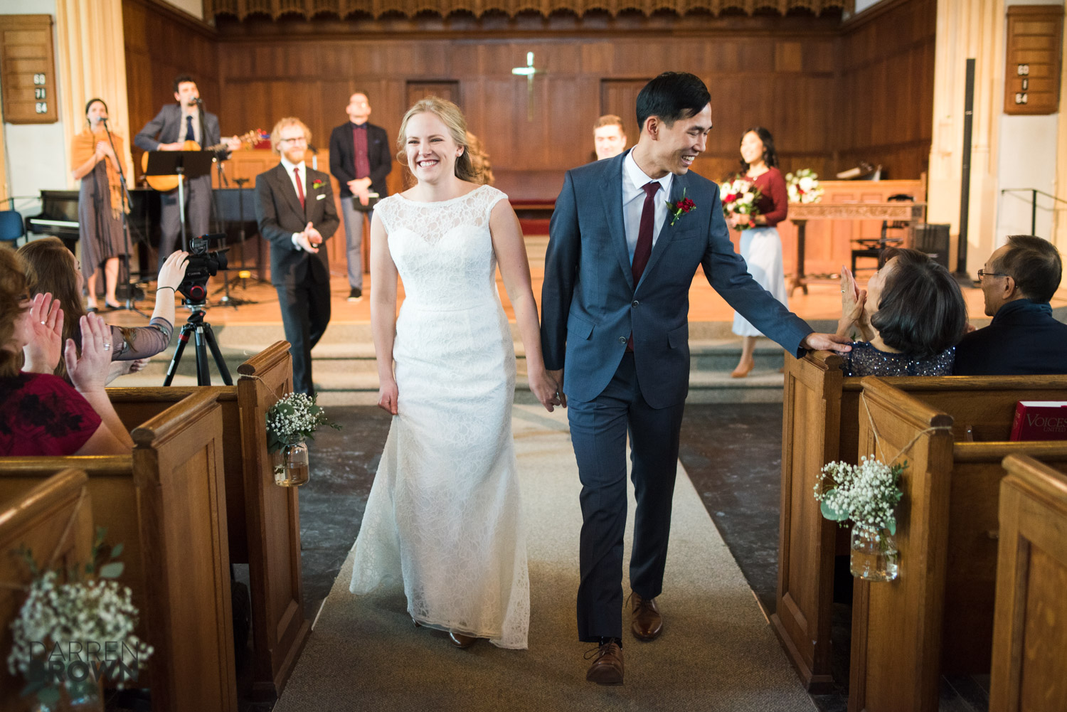 bride and groom walk down isle after getting married