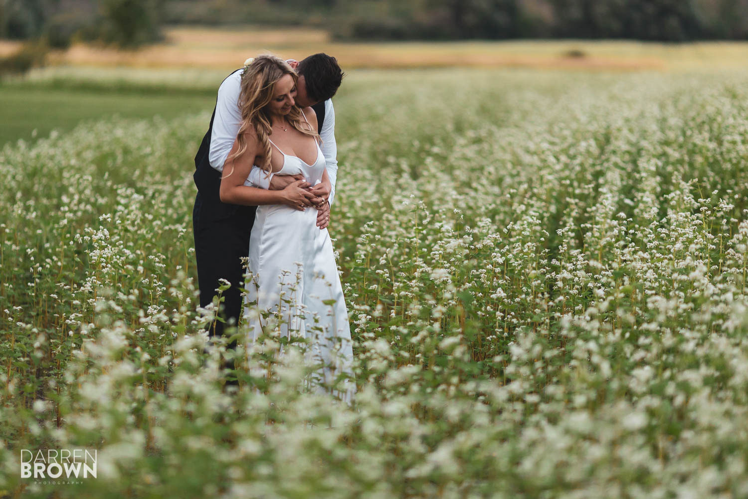 romantic evening portrait of bride and groom in field