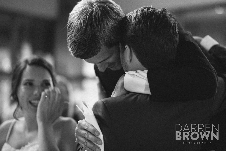 father hugs son at ottawa wedding reception
