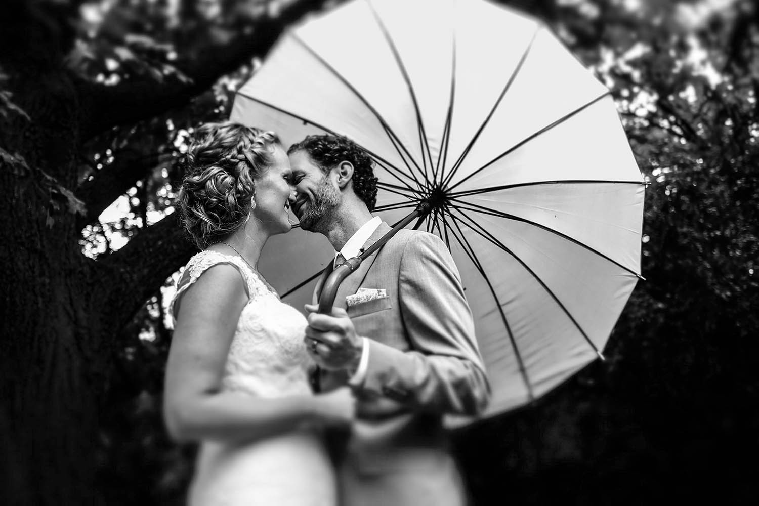 bride and groom kiss under a vintage umbrella during an Ottawa wedding
