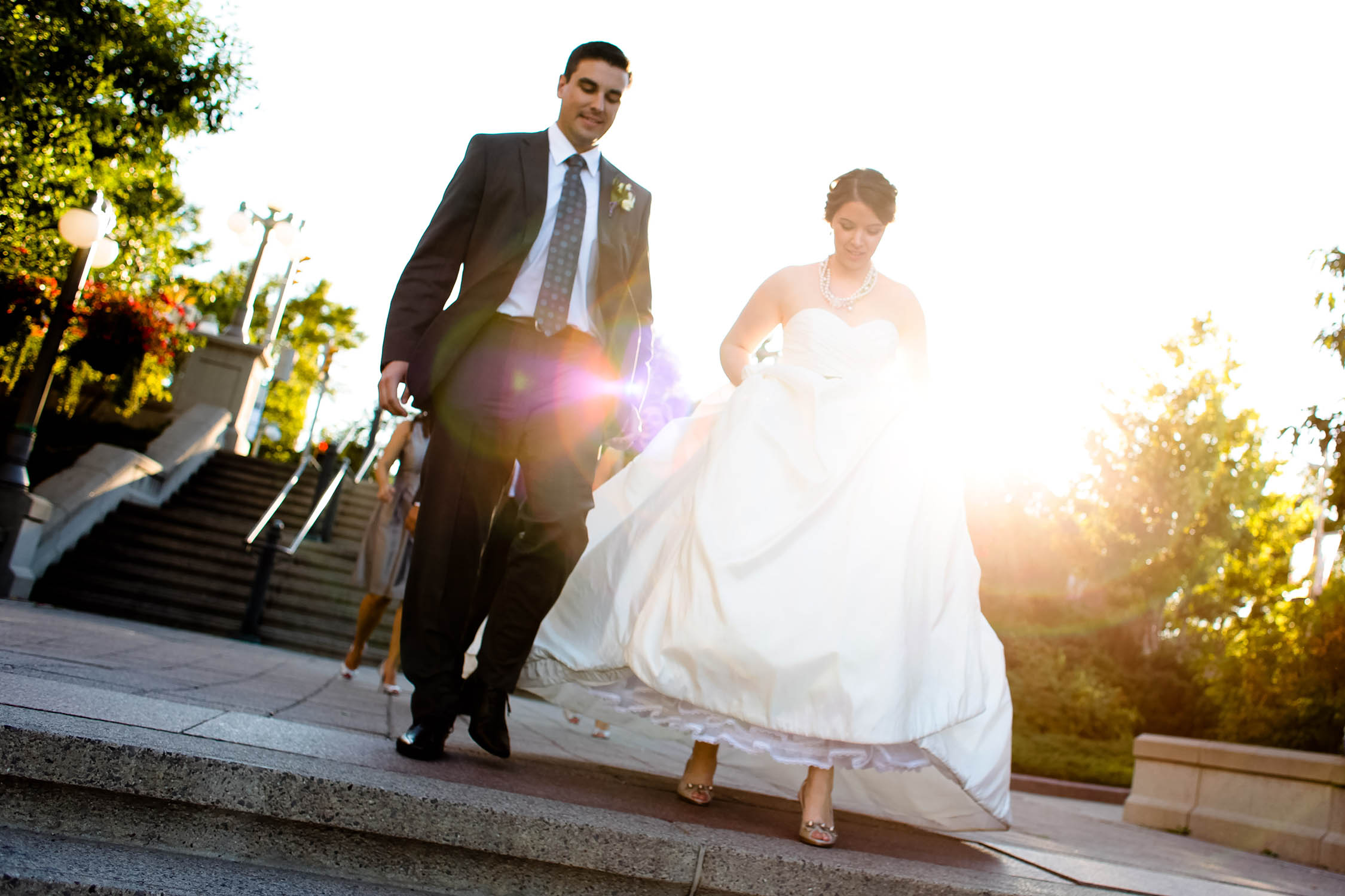 bride and groom walk down stone stair in ottawa wedding