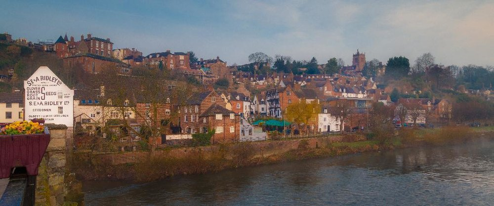 View of high town and Ridley Seeds signage from the bridge over the River Severn in Low Town, Bridgnorth