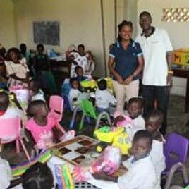 - Pictured is Dr. Robert Kalyesubula, along with the pre-school coordinator, and the children and the parents enrolled in the preschool program. The children are seated in tables and chairs donated by KLM Dutch Airlines.