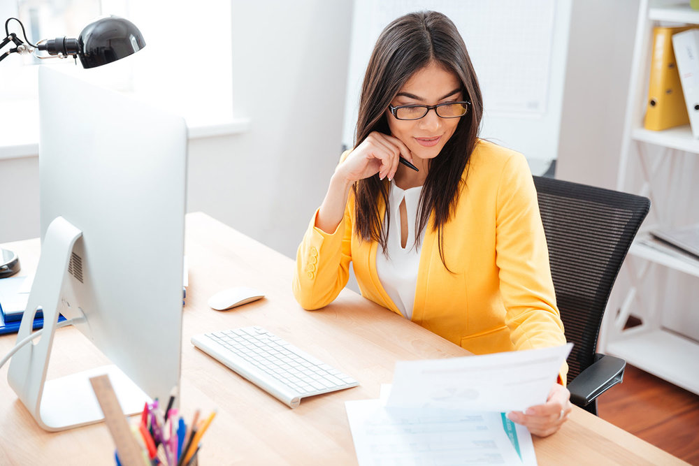 stock-photo-businesswoman-reading-paper-at-her-workplace-in-office-410727670.jpg