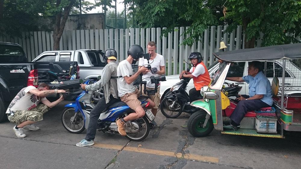 Ziemlich mit viel Risiko; Florian Wyss lässt sich auf das Moped binden, um anschliessend im Verkehr Bangkoks zu filmen...die ganze hilft dabei in den Vorbereitungen.