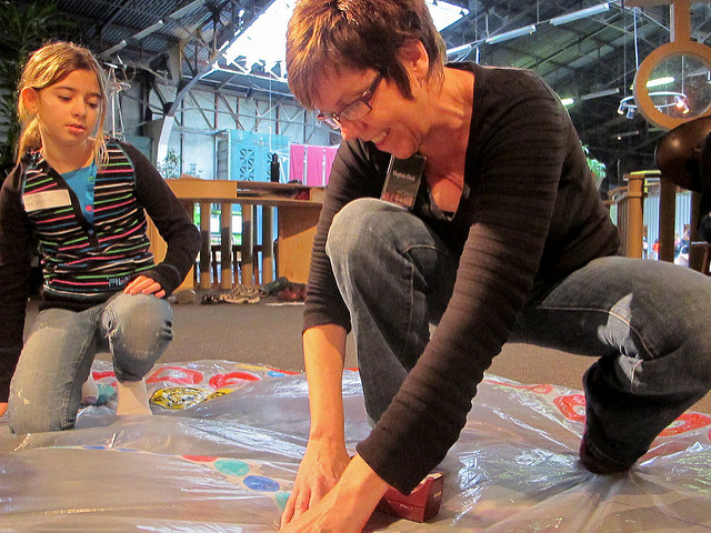 Virginia working with a young visitor, showing her how easy it is to tape decorative circles onto the piece.