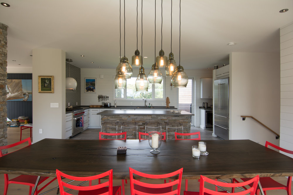 Open plan dining room and kitchen with red chairs and pendant lighting.
