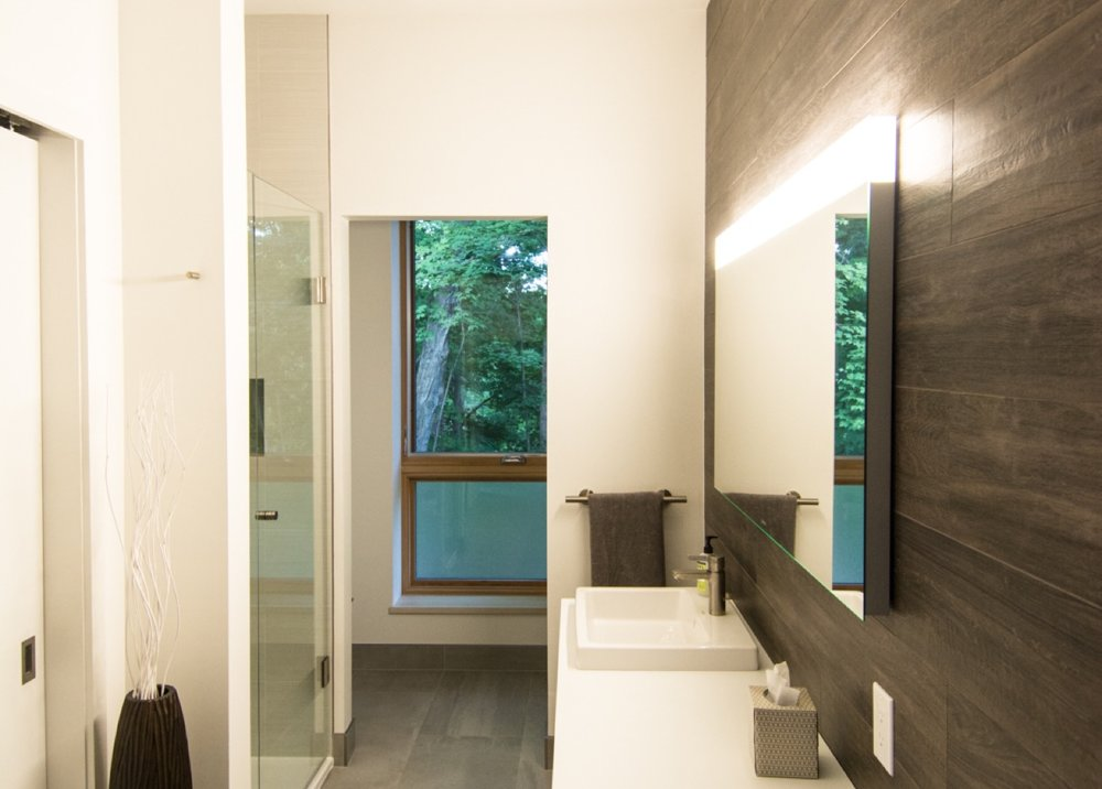 Modern bathroom with lighted medicine cabinet.