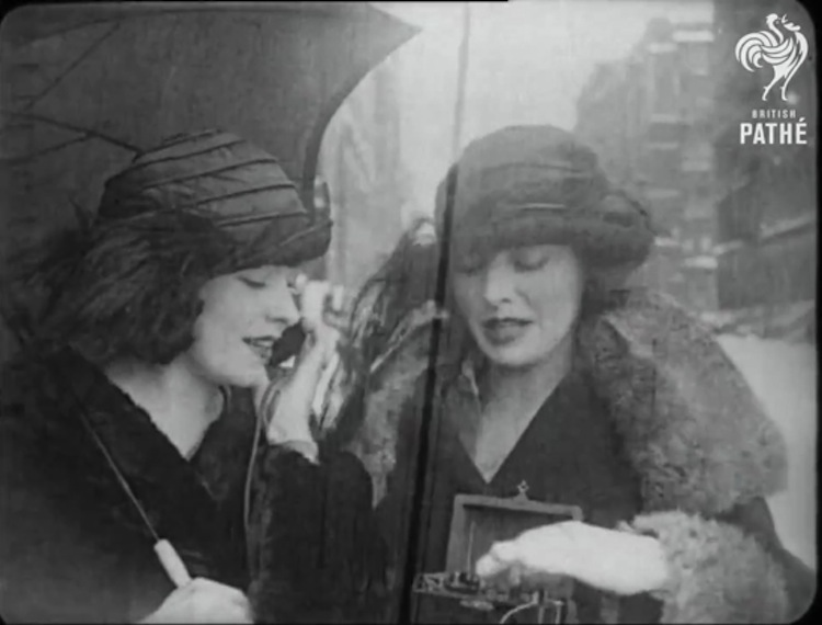 """Two women from the 1922 film """"Eve's Wireless"""" operating a portable crystal radio"""