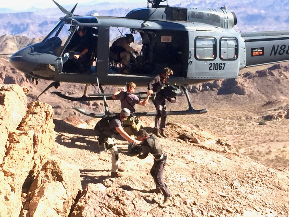 Crew using an iconic Huey helicopter to access a remote location in the Nevada desert.
