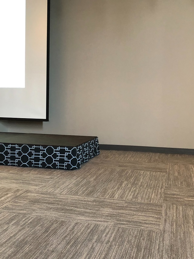 Seminar Room at the Boston Design Center using gray carpet tiles, gray painted walls, a version of Hale Navy and Decorators White on the platform skirt.