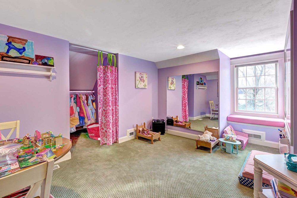This children's playroom has an art area and a full view mirror.