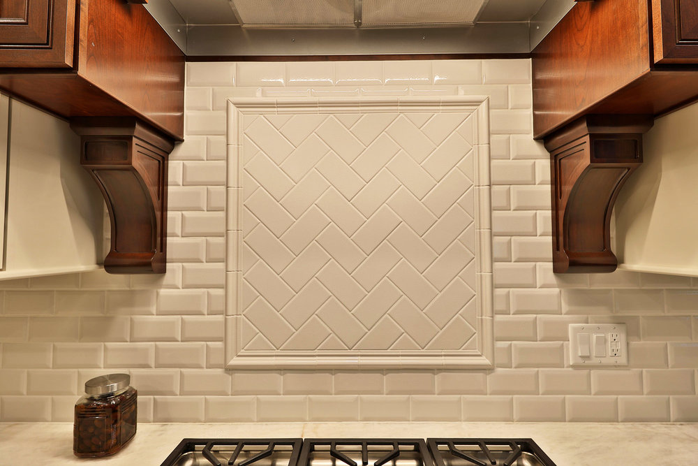 "The cooktop backsplash has a flat subway tile in 3"" x 6"" herringbone pattern backsplash and chair rail molding border."