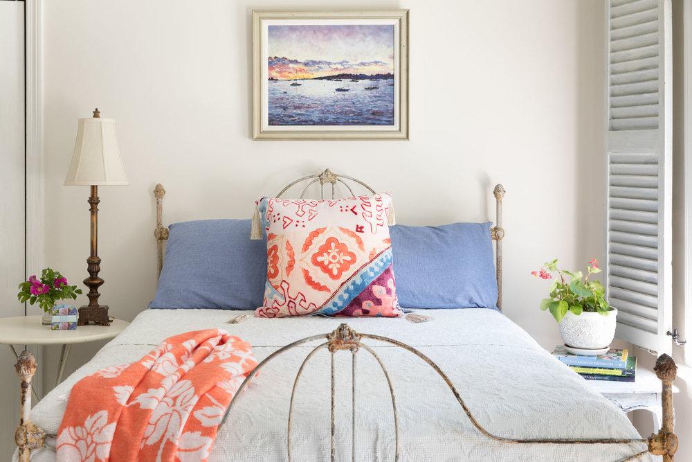 A vintage iron bed with an heirloom Martha Washington bedspread.