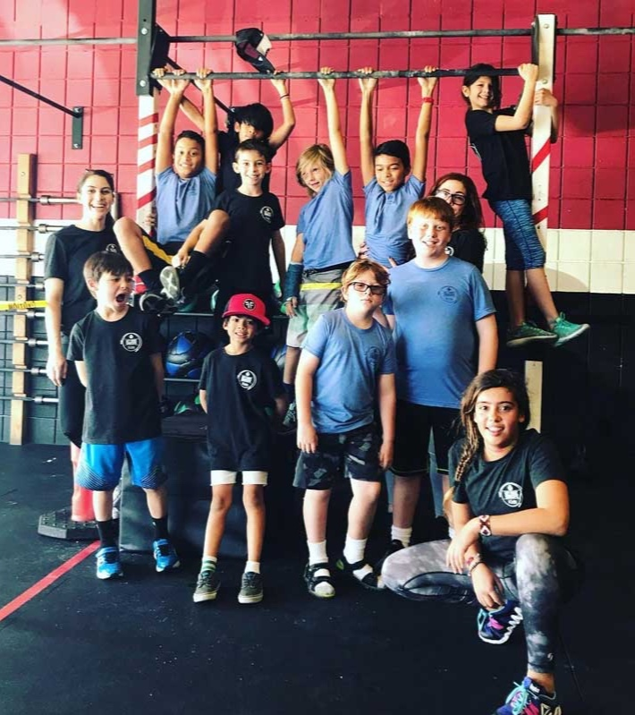 CROSSFIT KIDS PROGRAM - Our CrossFit Kids is a program is designed to teach CrossFit training methods to children ages 5-12. Based on the principle of Mechanics, Consistency and then Intensity, CrossFit Kids emphasizes good movement throughout childhood and adolescence. Consistently good mechanics translates to physical literacy, enhanced sports performance and fewer sports injuries for kids. Not only that, a vast body of research indicates that exercise is beneficial to cognitive function, which means consistent adherence to the program can have a positive impact on children's academic achievement.