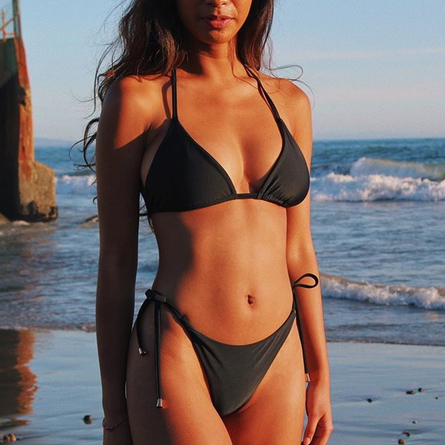 golden hour. in the string top x string bottoms in black 💫 ⠀⠀ suits made with regenerated nylon fabric from abandoned ocean fishing nets ♻️