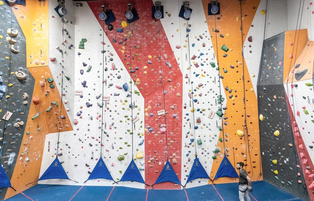 """Autobelays - These devices take up the rope (aka """"slack"""") as you climb, allowing you to scale routes without a partner. A special orientation is required to use the autobelays. Please see a Cliffs staff member to get one."""