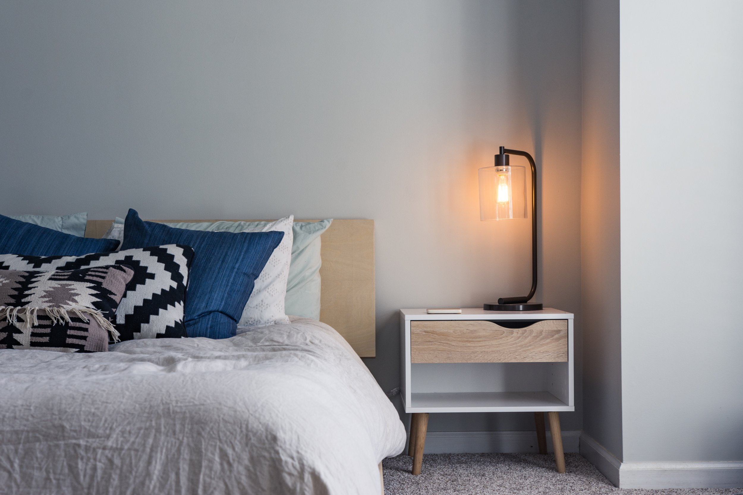Black lamp on wooden bedside table next to bed