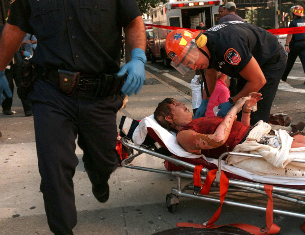 Burn victim Elaine Duch lies on a stretcher as she is tended to by FDNY EMT Moussa Diaz. (Jennifer S. Altman/WireImage)