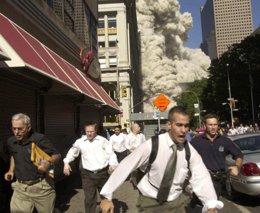 People flee from the plume of construction and other debris from the collapsing South Tower. (Suzanne Plunkett/AP)