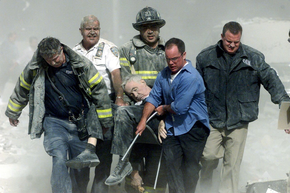 Rescue workers carry fatally injured Father Mychal Judge, the New York City Fire Department chaplain, after the collapse of the South Tower. (Shannon Stapleton/REUTERS)