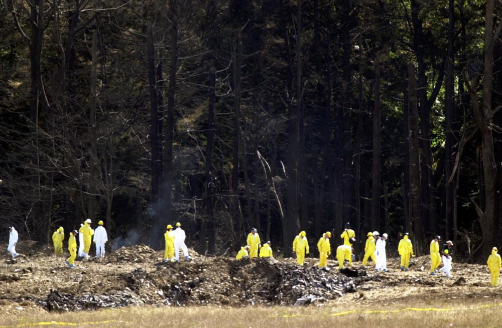 Investigators comb the debris field for the flight data recorders from United Airlines Flight 93 near Shanksville, Pennsylvania, on September 12, 2001. (Tim Shaffer/REUTERS)