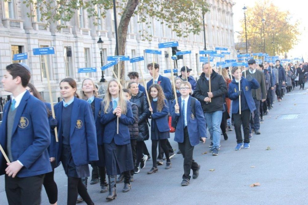 Pupils from JFS proudly holding aloft the names of alumni who died in WW1 at the 2018 AJEX Parade