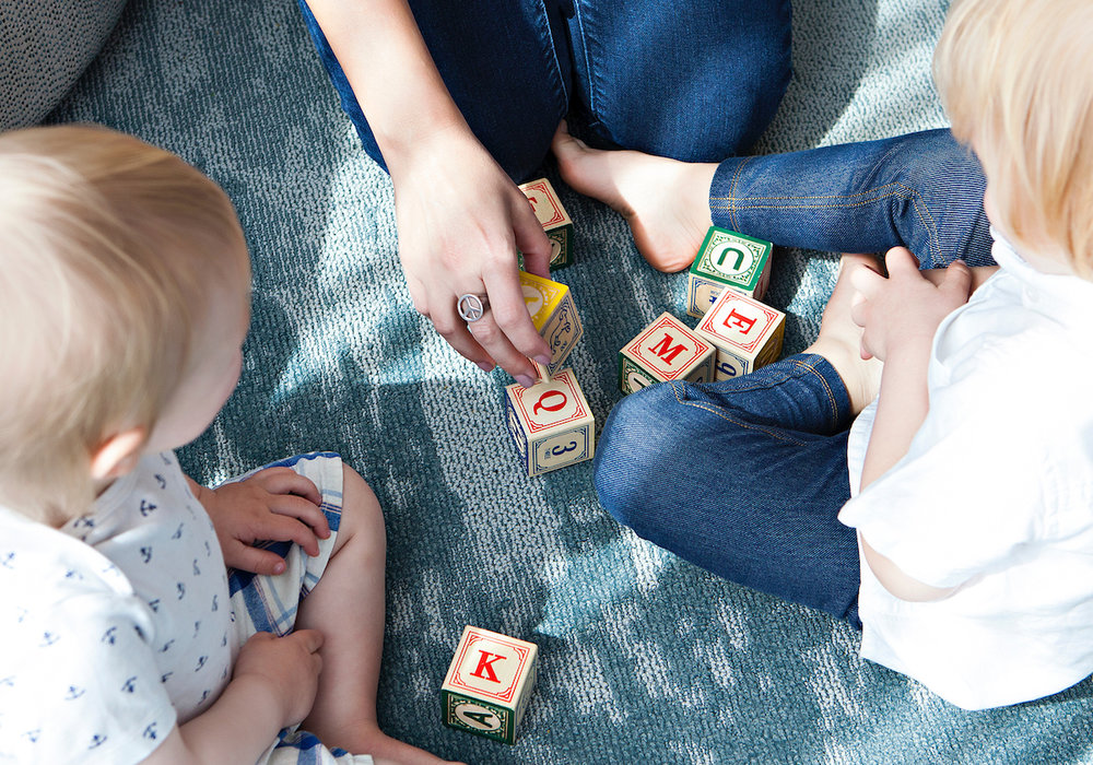 The time crunched parent playing with wooden blocks on the floor with two kids.