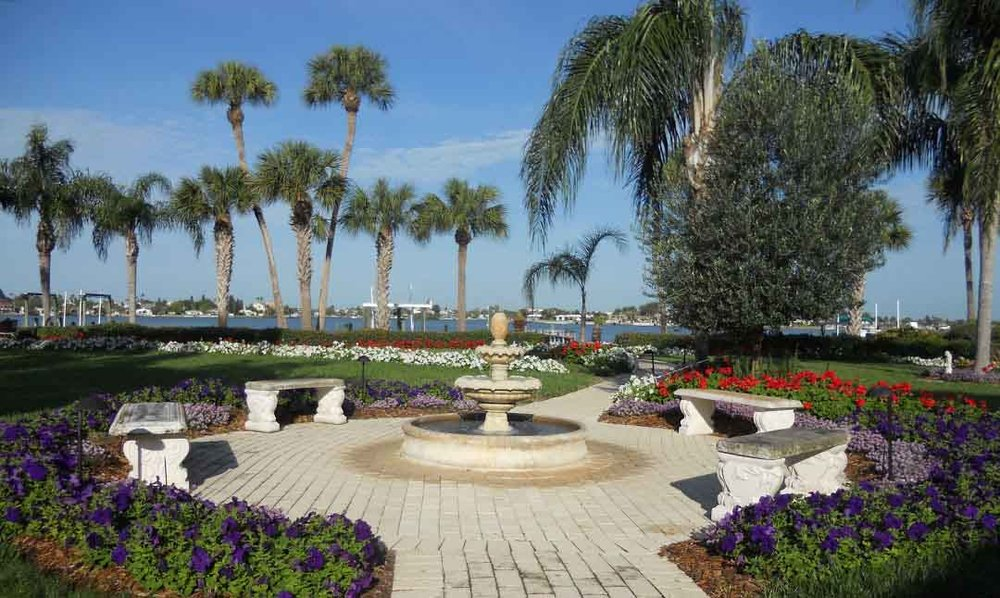Paver walkway with stone benches and fountain surrounded by beautiful flowering plants and palms