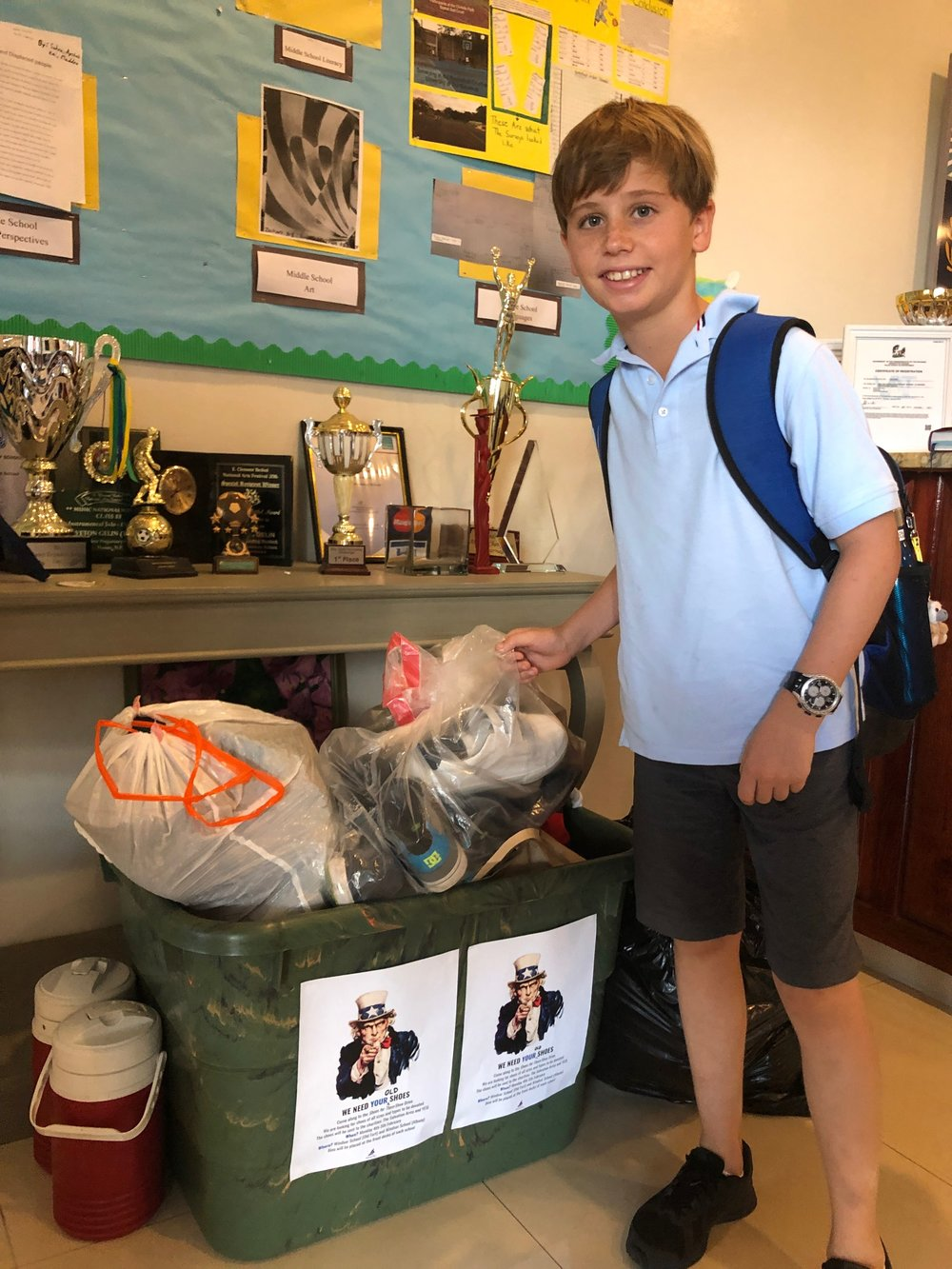 A happy Windsor student admiring the piles of shoes donated!