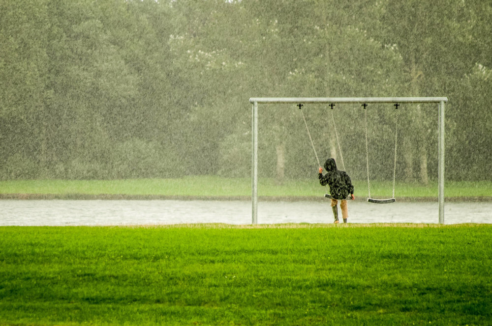 Kid on a swing in the rain