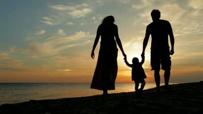 stock-footage-happy-family-walking-on-sea-coast-silhouettes-sunset.jpg