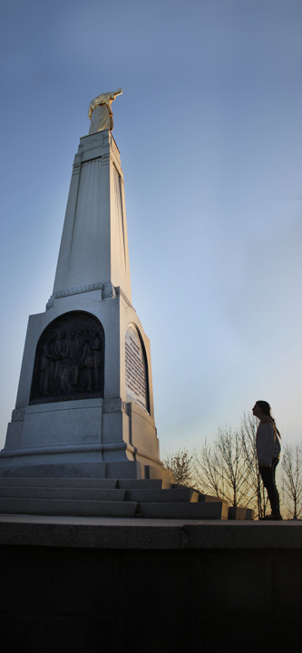 A girl stands attentively observing the Moroni statue.