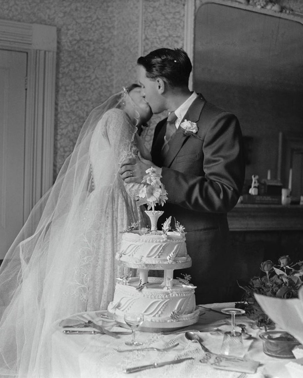 Vintage image of couple kissing by wedding cake